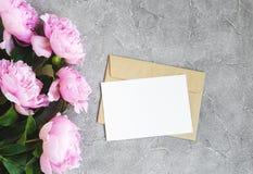 Inbjudankortet, hantverkkuvertet och rosa färgpionen blommar royaltyfri fotografi