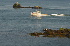 Inbound Lobster boat navigates among rocks. An inbound lobster boat navigates through treacherous waters and reefs between two rock outcrops Stock Photo