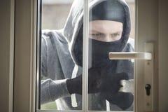 Inbreker Breaking Into House door Deur met Koevoet Te dwingen stock afbeelding