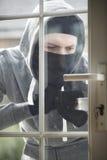 Inbreker Breaking Into House door Deur met Koevoet Te dwingen stock afbeeldingen