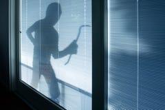 Inbreker die balaclava dragen die door venster kijken royalty-vrije stock fotografie