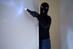 Inbreker die een balaclava holdingsflitslicht dragen stock afbeeldingen