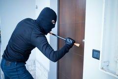Inbreker die een deur proberen te dwingen Stock Fotografie