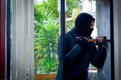 Inbreker met koevoet die onderbreking proberen het venster om het huis in te gaan stock fotografie