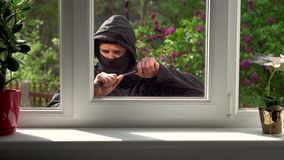 Inbrekeronderbrekingen in een huis door het venster stock video