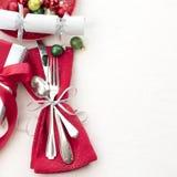 Inbrott för jultabellställe som är rött som är vitt och silver med bestick, en gåva och partismällare på vit torkdukebakgrund med arkivfoton