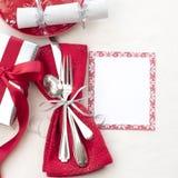 Inbrott för jultabellställe som är rött som är vitt och silver med bestick, en gåva och partismällare på vit torkdukebakgrund med royaltyfri foto