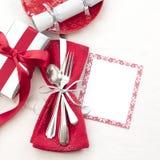 Inbrott för jultabellställe som är rött som är vitt och silver med bestick, en gåva och partismällare på vit torkdukebakgrund med royaltyfri fotografi