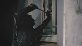 Inbrottstjuv med kofotavbrottsdörren som skriver in huset
