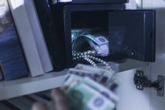 Inbrottstjuv som tar pengar och halsbandet royaltyfri foto