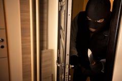 Inbrottstjuven bryter in i en lägenhet royaltyfri foto
