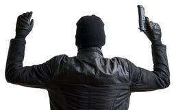 Inbrottstjuven som maskeras med balaclavaen, sätter upp händer och ger upp Arkivbild