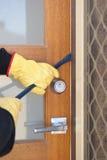 Inbrottstjuv som bryter i hus med kofoten på dörren arkivbild