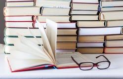 Inbunden bokböcker på den vita trätabellen, den öppna boken och exponeringsglas, kopieringsutrymme för text royaltyfria foton