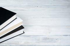 Inbundna boken bokar på trätabellen, vit bakgrund tillbaka skola till Kopiera utrymme för text Utbildningsaffärsidé Royaltyfri Fotografi