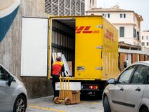 Senior worker discharge DHL parcels from truck in central square. INCA, PALMA DE MALLORCA, SPAIN - MAY 8, 2018: Senior DHL postmen delivering post parcels from royalty free stock images