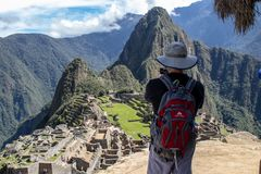 The Inca Ruins at Machu Picchu. A tourist gazing at the stunning Inca ruins at Machu Picchu, Peru with its assortment of intact stone buildings built on multiple royalty free stock photography