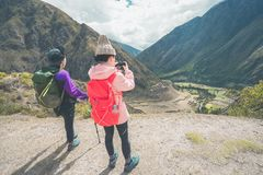 Inca Trail, Peru: August 11th, 2018:Two young female hikers are taking photos on the famous Inca Trail. They will need to walk 4 stock photography