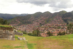 Inca Walls and Cuzco town on the background. The walls of the old Inca fortified sacred town of Saqsaywaman, on the hills above Cuzco royalty free stock photos