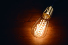 Incandescence classic bulb. Edison incandescence classic styled bulb on wooden board background Royalty Free Stock Photo