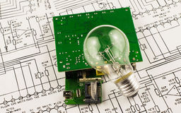 Incandescence  lamp and chip. On the background drawings of microcircuits Royalty Free Stock Images