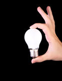 Incandescent bulb in hand on black Royalty Free Stock Photography
