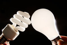 Incandescent and cfl lightbulb on black. An incandescent and cfl light-bulb facing each other on a dark background stock photo