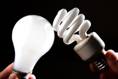 Incandescent and cfl lightbulb on black. An incandescent and cfl light-bulb facing each other on a dark background royalty free stock photography
