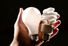 Incandescent and cfl lightbulb in human hand. An incandescent and cfl light-bulb in human palm backlit royalty free stock photo