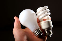 Incandescent and cfl lightbulb in human hand. An incandescent and cfl light-bulb in human palm backlit royalty free stock image