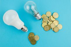 Incandescent lamp and energy saving on a blue background. Copy space stock photography