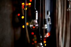 Incandescent lamp. Incandescent light in a dark room and multicolored glare Royalty Free Stock Photos