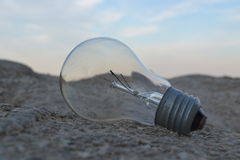 Incandescent Lamp. The old incandescent bulb on the coastal rock. Fading technology Royalty Free Stock Photography