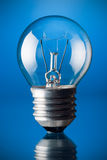 Incandescent light bulb. On blue background stock photos