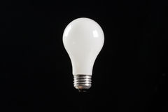 Incandescent light bulb black background Stock Images