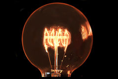 Incandescent light bulb. Close Up Of An Illuminated Vintage Hanging Light Bulb Over Dark Background Stock Photo
