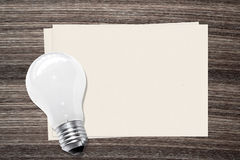 Incandescent light bulb and and paper on wood background Royalty Free Stock Image