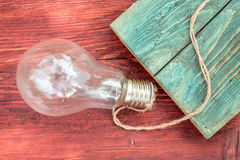 Incandescent light bulb with rope. Incandescent light bulb electric glass with rope on wooden background stock photography