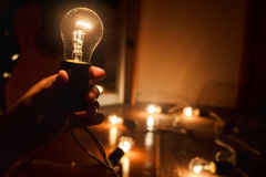Incandescent light bulb, warm turned on. Garland of tungsten lamps. Light in darkness, copy space. Royalty Free Stock Photos