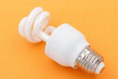Incandescent light bulb. Incandescent energy saving bulb on orange background Stock Photography