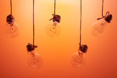 Incandescent light bulbs hanging on a orange background Stock Photos