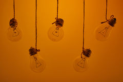 Incandescent light bulbs hanging on a yellow background Stock Photography