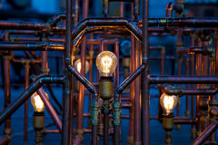 Incandescent light bulbs between pipes. Beautiful art work with complicated rusty pipes and bulbs Royalty Free Stock Photography