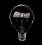 Incandescent Lightbulb with Bundle of Money Inside Stock Photos