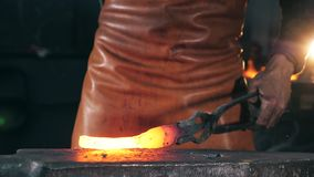 Incandescent metal element is getting forged. Slow motion. Incandescent metal element is getting forged. HD stock video footage