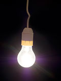 Incandescent old style light bulb, on black, with genuine rays. Royalty Free Stock Photos
