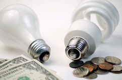 Incandescent Versus CFL Lightbulb. Difference in savings between old incandescent bulbs and newer CFL Bulbs. Dollars versus cents to use Stock Photography
