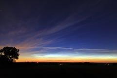 Incandescenza di alba di primo mattino riflessa in nuvole esili immagine stock libera da diritti