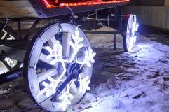 Incandescer as rodas, festão do Natal sob a forma dos flocos de neve no carro de madeira roda foto de stock