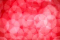Incandescer borrada do bokeh circunda no fundo vermelho fotos de stock royalty free